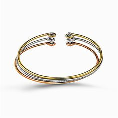 Reflecting an eye-catching but simple contemporary design, this three-tone open-style bangle bracelet is accentuated by .22 ctw of white diamonds. Print Page