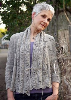 TriticumThis luxurious little open-front cardigan transitions with ease from cocktails with a little black dress to kicking around in jeans at the beach—you won't want to leave home without it. With an elegant sweep of openwork down the center front, it flatters every one of its eight sizes (from XS to 4X) with subtle shaping that skims the body. The cable and lace motif is repeated at the back waist and sleeves, which may be knit full or elbow length. Its five simple to knit piece are…