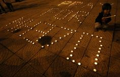 """A girl lights a candle next to a message that reads """"Pray for MH370"""" during a candlelight vigil held by ethnic Malaysian Chinese for the passengers of Malaysia Airlines MH370 near Independence Square in Kuala Lumpur March 10, 2014. Reuters/Edgar Su"""