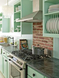 love the color, plate rack, milk glass, ironstone, grey counter- whatever it is? concrete or granite, faucet..not the brick though. white subway tile would make it perfect