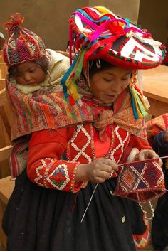 Mother Andean knitter and knitting with baby on back, wearing chullo hand-knit cap. http://creavitalite.canalblog.com/archives/2015/08/14/32487740.html#comments