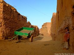 A lone green wagon in a sea of golden desert. Mut, Egypt.