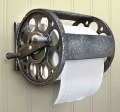 Fishing reel toilet paper holder hanging on wall