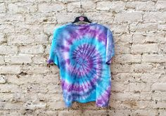 Hippie shirt, tie dye tshirt, trippy, psychedelic style! Unisex t-shirt, all sizes available.  Whether chilling at a festival or out with friends, this striking, top with its bright purple & blue tie dye colours will ensure you stand out from the crowd.  This cool one of a kind tshirt was hand dyed in July 2015... upcycled from a plain white tshirt...remade with love by AbiDashery.  SIZES - XS,S,M,L,XL,XXL - custom made to order please state size at checkout.  The chest measurements are as…