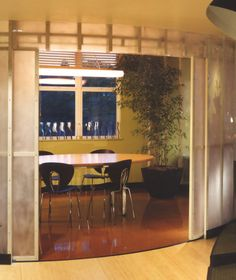 Conference room with translucent sanded acrylic walls and curving pocket doors constructed of steel tubing and acrylic, this little gem of a room lets natural daylight through at daytime, and glows from the inside at night.