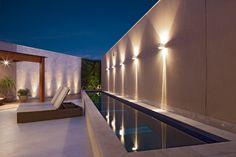 """Com 40 m², esta piscina em forma de raia - construída na área de lazer de uma residência pela arquiteta Estela Netto - tem estrutura de concreto armado. Segundo Netto, """"o revestimento de vinil é mais barato e mais prático, no entanto a pastilha de vidro, como a deste exemplo, é oferece maior variedade de cores"""". A borda da piscina é de granito branco e o destaque fica por conta da iluminação com arandelas e a parede verde, ao fundo"""