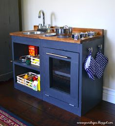 Earning Our Stripes: DIY Play Kitchen  Paint can lids were used for the burners.