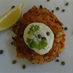 Chef John's Salmon Cakes  Allrecipes.com1 (14.75 ounce) can red salmon, skin and bone removed, drained and flaked  2 eggs  1/2 lemon, juiced  1 tablespoon chopped capers  1/2 teaspoon salt  1/2 teaspoon ground black pepper  1/2 teaspoon cayenne pepper  12 saltine crackers  1 tablespoon bread crumbs, or as needed  1 tablespoon butter  1 tablespoon olive oil