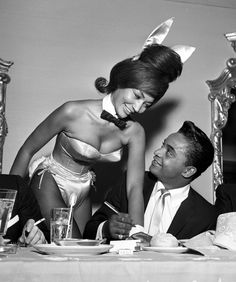 Rock and roll singer Jackie Wilson autographs the cuff of a Playboy Bunny at a dinner for the Motion Picture Pioneers Association at the Playboy Club on November 19, 1962 in New York, New York.