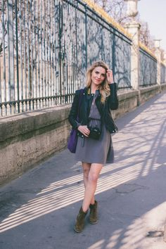 Spring outfit idea. Leather jacket, dress, purple bag, and brown boots. Perfect spring style.