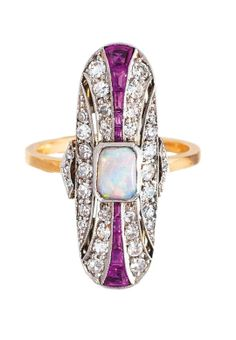 An Art-Déco opal diamond ring with ruby setting C. 1920. 18 ct. yellow gold, platinized. Long ringtop with one central opal (5,5 x 4 mm) and on the sides 10 rubies in baguette and trapez cut in total c. 0,50 ct. and with 36 diam. in 8/8- and rosecut in total c. 0,80 ct. H-I.vsi-si. Ringtop 28 x 12 mm, size 54, weight c. 5 g.