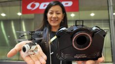 Wearables, drones, talking robots take center stage at International Tokyo Toy Show | A CCP Co. employee shows off the Nano Falcon DigiCam, a remote-controlled copter that can shoot photos or videos from the air. The 20-gram drone can also be folded up an