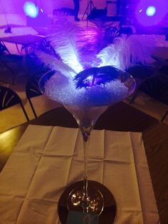 60cm tall martini glass filled with pebble raindrops and peacock feathers in royal blue and white, lit up with immersive led lights.   by Made Marvellous
