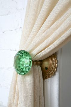 Glorious idea: use vintage glass door knob for curtain tie back!