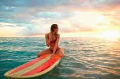 Pacific Islander woman floating on surfboard in ocean - Pacific Islander woman floating on surfboard in ocean