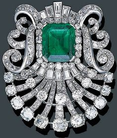 A VERY FINE ART DECO PLATINUM, EMERALD AND DIAMOND BROOCH, MAUBOUSSIN. Centring on a rectangular-cut Colombian emerald weighing approximately 10.76 cts. within an old mine-cut border to the scrolling diamond set surround, mounted in platinum, circa 1925, signed Mauboussin, Paris. #Mauboussin #ArtDeco #brooch