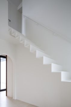 A thin metal staircase provides access to the renovated attic space of this house in Belgium.