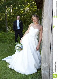 Beautiful bride poses for portrait with husband in the background.