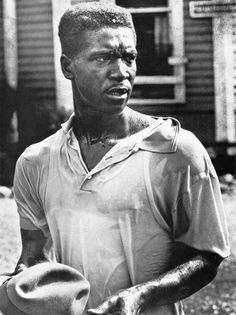 A Birmingham Civil Rights activist glares at the firemen who have just assaulted him with a water hose, 1963