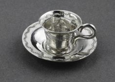 """19th Century Antique Dutch Miniature Silver  Teacup and Saucer Set (6 of each) A lovely set of 6 miniature silver teacups with matching saucers, both cups and saucers are decorated with a hand engraved zig zag pattern. This is around the rims and centre of the saucers, and both inside and outside the rims of the teacups. All 6 saucers have 2 hallmarks, firstly makers mark """"H goblet"""" in a 6 sided punch, we have not been able to identify the maker (we would welcome assistance, thanks!)."""