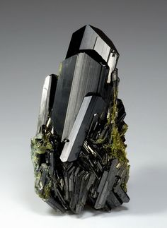 Epidote, Ca2Al2(Fe3+;Al)(SiO4)(Si2O7)O(OH). The anisotropy, or directional asymmetry, of epidote causes the stone to appear different colors from different directions. The crystal structure bends light differently depending on the path, appearing to you as a color change. This picture shows a bluish-green for the crystals on the left, and a more yellow-green on the right.