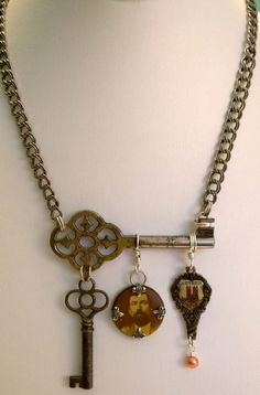 Found object assemblage necklace created by Renee Webb Allen featuring antique skeleton keys, celluloid tin button and souvenir London spoon top. Small Stuff Design