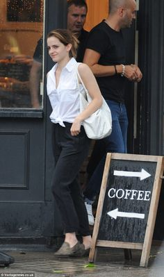 Effortlessly elegant: Emma Watson meets a friend for a coffee in central London wearing a tie top and black slacks.