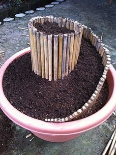 Simply get a large flower pot (like the one shown) and bamboo Break the bamboo into equal lengths. Fill the pot with soil to about just an inch and a half from the brim. Begin pushing in the bamboo sticks close together starting at the TOP and working your way down into a spiral, trimming the bamboo as needed and keeping them close together.Add more soil once your bamboo spiral is constructed.