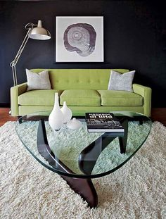 Retro-modern Noguchi coffee table on shag rug and green apple sofa.