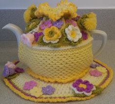this unique large 6 cup tea cosy and mat set is hand knitted, crocheted and beaded to my own design....  the cosy is knitted in doubled double knitting in a soft lemon...it has a honeycomb stitch and stocking stitch body.....with a fluted and frilled top edged in a darker yellow....there is a row of cream crochet across the cosy and a pretty darker yellow frill at the bottom edge....  i crocheted a cord in meadow green which threads through and wraps around the top of the cosy ...  i…