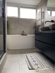 Prachtige industriële badkamer. Hier is gebruik gemaakt van betonlook tegels. Mat zwarte benodigdheden passen hier perfect bij. Daarnaast zie je subtiele natuurlijke hints terug, zoals de natuursteen waskommen. | ARTIKELNUMMERS:  Tegel: JSBETONLOOKGRIJS Wandtegel (douche): 1527410 Bad: 21.3651 Meubel: TOP1425SET Waskom: 36.102.03 Radiator: 41.3510 Badkraan: 29.2932 Wastafelkraan: 29.2151 Regendouche: 29.2956  Bathroom Inspiration, Home Decor Inspiration, Bungalow, Home Goods, Sweet Home, Bathtub, Patio, Interior Design, Shower