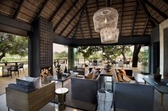 Designed for Megan Ralph Spaces for a safari guest lodge, these beautiful matte black ceramic wall tiles create visual intrigue above the fireplace in the guest area whilst beautifully complimenting the rest of the interior design.  #ceramic #wallpaper #design #interiordesign #architecture #southafrican #guesthouse #safari #decor #fireplace #tiles #wall #walltiles #featurewall #designideas #designinspo #homerenovations #hotel #renovations #bar