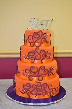 """4 tier wedding cake, Orange with purple and silver accents. Tiers are 12"""", 10"""", 8"""" and 6"""", each about 4"""" tall. Adap..."""
