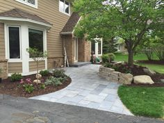 New front patio/entryway with Silver Creek Blue-stone Slate Pavers and a Chilton natural stone seating wall.