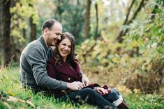 Giggling couple sitting on the grass engagement photo
