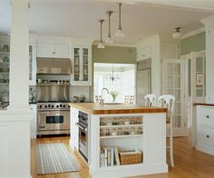Airy white kitchen with glass front cabinets butcher block island open floor plan upper shelving spice storage oven in island. Kitchen Inspirations, Kitchen Remodel, Kitchen Countertops, New Countertops, New Kitchen, Kitchen Island Design, Cottage Style Kitchen, Home Kitchens, Kitchen Renovation