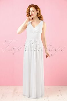 You'll have the best day of your life when wearing this 50s Mila Empire Maxi Dress of the East of Eden collection!Deep V-neckline, a playful waist band and a sexy slit at the front, wow! Made from a flowy ivory white, semi-sheer fabric (doesn't stretch!) and fully lined. Whether it's your wedding, a party or a Red Carpet occasion... Mila will make you shine like never before!    Sewn in soft cups Crossed waist band Fully lined Smock at the back No zipper or buttons Pleated skirt Ou...