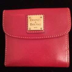NWT Dooney & Bourke red leather wallet Beautiful red leather billfold from Dooney & Bourke with the logo on a small brass plaque and white contrast stitching around the edges. New with tags, but no box. There is a small scratch on the flap near the logo as seen in picture one. I bought it that way, although a little red leather polish could probably hide it pretty well. Registration card is also included. P.S. Red wallets are considered very lucky by the Chinese, and I have found it to be…
