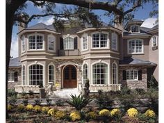 Eplans House Plan: The grand entrance to this elegant European-style home is flanked by window bays stacked two high. The two-story foyer opens immediately to a formal dining room and study; straight ahead is the entry to the