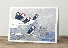 A pack of 10 illustrated Christmas / Holiday cards featuring a wintery scene with puffins and snow. - 5x7 standard size Greeting Cards - Printed on