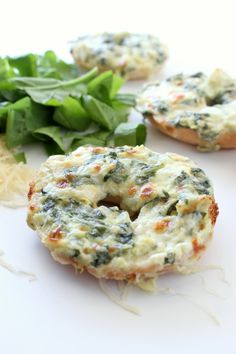 Spinach and Artichoke Dip baked on top of mini bagels. The classic dip gets a makeover in these cute little appetizers, Spinach and Artichoke Bagels. From @chocolatewgrace
