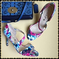 """Strap Sandal Heels NEW IN BOX Spring/Summer floral pink/multicolored print faux patent leather upper with a gorgeous asymmetrical strap with an elastic insert for stretch fit! Perfect for sundresses, capris, jeans! Cushioned insole, 3 1/4"""" covered heel, synthetic sole. You'll want to wear these beauties all the time! Size 9M Unisa Shoes Sandals"""