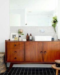 Mozaïektegeltjes tussen spiegel en lavabo.