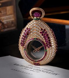 "Vacheron Constantin. An unique 18ct gold diamond ruby and emerald manual wind hunter pocket watch  ""Mysterieuse"", Circa 1988 - transparent ""mystery"" dial with polished gold hour and minute hands, polished 18ct gold pear shaped case set throughout with round diamonds and pear-shaped rubies, crown set with carved ruby bead, decorated by baguette-cut emeralds"