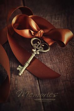 Brass key with satin ribbon on wood | Memories Sandralise Cunningham Photography