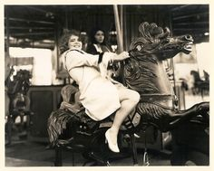 Clara Bow photo by Otto Dyar, circa 1928. Reverse photo caption says: A WILD WESTERN REDHEAD - When it comes to amusement places & wild, dangerous rides, Clara Bow, Paramount screen star, loves to ride on an old fashioned merry-go-round.
