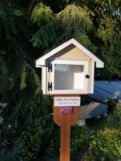 Tucked under a tree near an already-existing concrete bench in a beautifully landscaped garden niche, this little free library mini-me was designed to match one of the more prominent dormers on the customers' home on North College Place Drive in Spokane, WA. Built by Little Library Builder of Spokane! www.littlelibrarybuilder.com Little Free Libraries, Little Library, Free Library, Concrete Bench, College, Building, Mini, Places, Garden