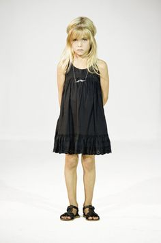 She looks depressed. But its a cute little black dress for baby k <3