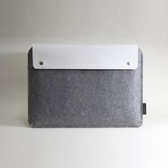 This designer laptop sleeve combines minimalism with long lasting elegant accents, it features a mixture of unique white leather and grey wool felt, also a snap fastener closure. It can keep you...