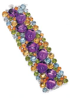 *18 KARAT WHITE GOLD, AMETHYST, AQUAMARINE, PERIDOT, MANDARIN GARNET AND DIAMOND BRACELET The highly flexible strap centering a row of nine cabochon amethysts, accented by smaller cabochon citrines, peridots, aquamarines and mandarin garnets, further set with round diamonds.